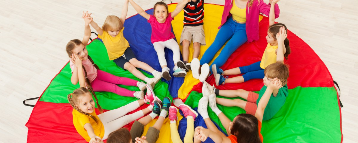 Top view portrait of young nursery teacher playing circle games with preschool children, holding hands together, sitting on rainbow parachute